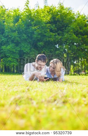 Happy Caucasian Couple In Love Lying On The Grass Outdoors. Reading Personal Ebook Reader.