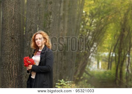 Beautiful Woman With Red Rowanberry Stands In Autumn Park At Sunny Day