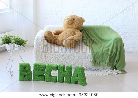 Room With White Couch, Toy Bear And Green Text On Floor: Spring