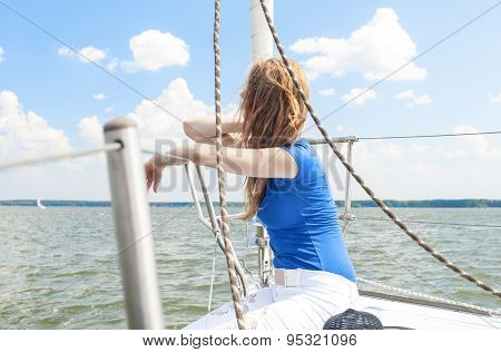 Portrait Of Young Caucasian Woman Travelling Under Sail On Water