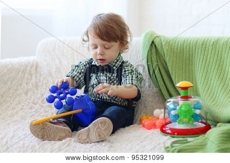 Little Handsome Happy Boy Sits On Soft Sofa And Plays With Toys