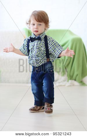 Little Handsome Curly Boy Stands With Arms Outstretched In Light Room
