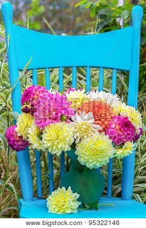 A vase of dahlia cut flowers on a pretty blue chair in the garden.
