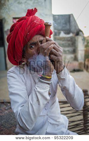 GODWAR REGION, INDIA - 12 FEBRUARY 2015: Rabari tribesman smokes chillum. Rabari or Rewari are an Indian community in the state of Gujarat.