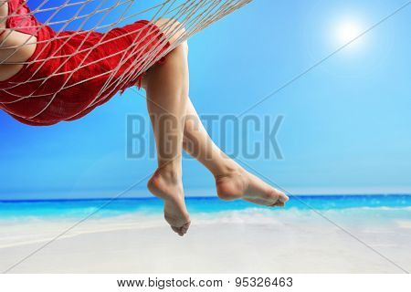 Close-up on the legs of a woman lying in a hammock on a beach by the open sea
