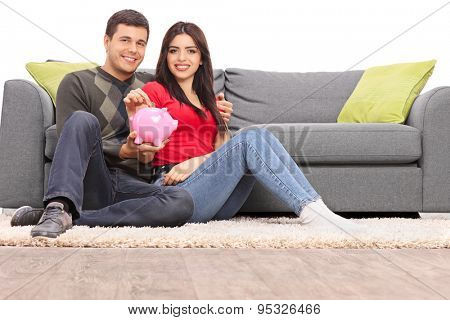 Young couple sitting in front of a modern gray sofa and holding a piggybank isolated on white background