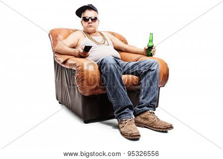 Senior man in a hip-hop outfit sitting in an armchair and holding a remote control isolated on white background