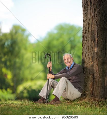 Casual senior man holding a cane and sitting on grass in a park and looking at the camera shot with tilt and shift lens