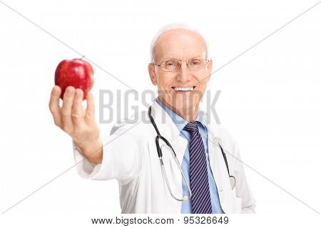 Cheerful mature doctor in a white coat handing a red apple towards the camera isolated on white background