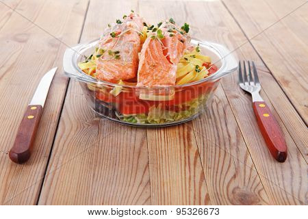 fresh fried natural pink salmon on italian traditional tagliatelle backed with tomato and vegetables served over wooden table with cutlery