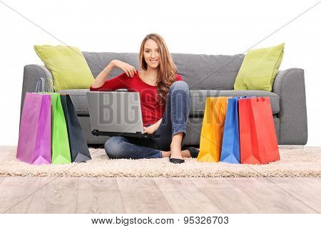 Young woman holding a laptop seated in front of a modern gray sofa with a bunch of shopping bags on the floor around her isolated on white background