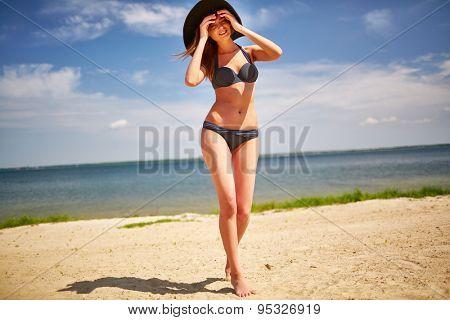 Happy girl in bikini and hat walking down sandy beach