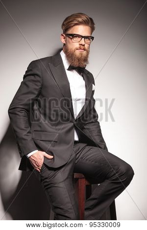 Young blond business man looking at the camera while resting on a stool with his hand on pocket.
