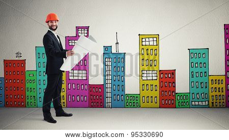 smiley man in orange hardhat with blueprint over grey wall with variegated drawing houses