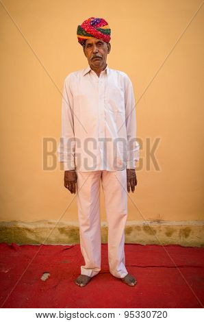 GODWAR REGION, INDIA - 15 FEBRUARY 2015: Elderly Indian man poses in-front of blank wall on red carpet wearing white outfit and colorful turban for wedding.