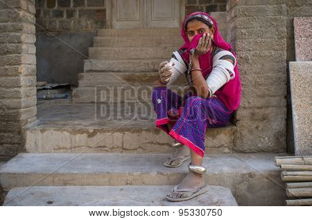 GODWAR REGION, INDIA - 15 FEBRUARY 2015: Indian tribeswoman covers face with headscarf and sits in front of home in saree decorated with upper-arm bracelets.