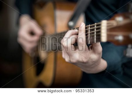 Young man play on the acoustic guitar