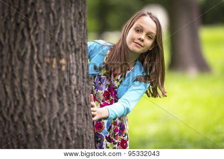 Cute little girl peeking from behind a tree.