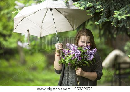 Teen girl with a bouquet of lilacs, standing under an umbrella in the garden.
