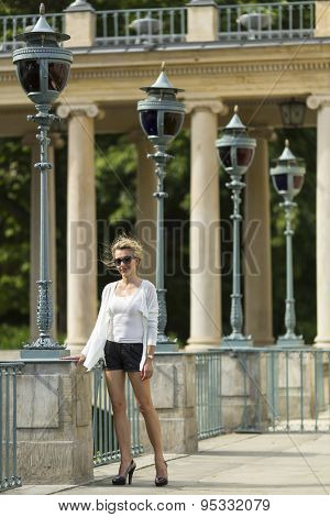 Beautiful young woman standing in the Royal Baths Park in Warsaw.