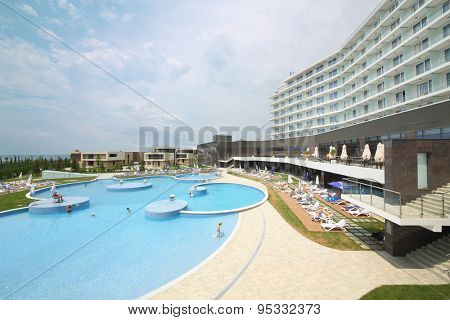 SOCHI, RUSSIA - JUL 27, 2014: People sunbathing on loungers around big pool on the territory of the Hotel Radisson Blu Paradise Resort and Spa