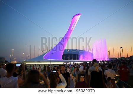 SOCHI, RUSSIA - JUL 27, 2014: Crowds of tourists walking near a bowl of the Olympic flame and singing Fountain in the Olympic park in the evening