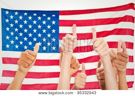 Hands up and thumbs raised against rippled us flag