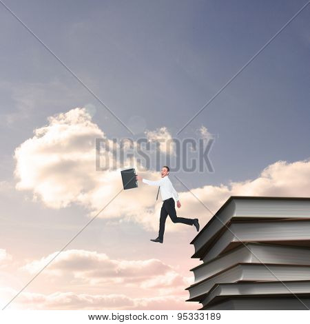 Happy businessman leaping with his briefcase against blue sky with white clouds