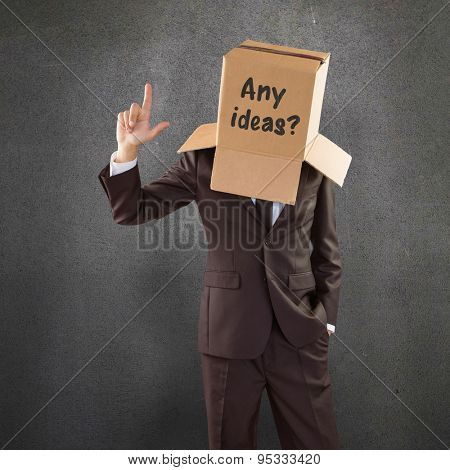 Anonymous businessman pointing up with finger against grey room