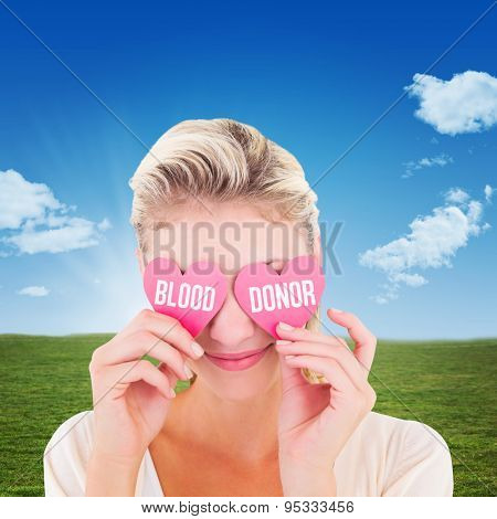 Attractive young blonde holding hearts over eyes against blue sky over green field