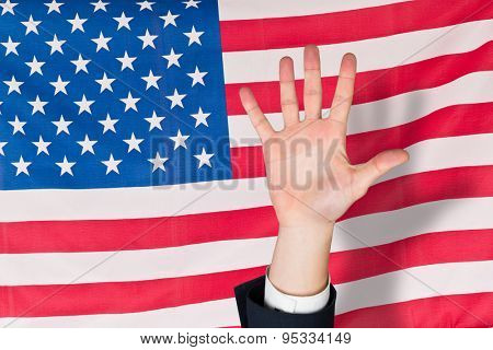 Hand with fingers spread out against rippled us flag