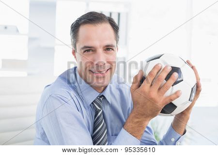 Smiling businessman looking at camera with foot ball in his office