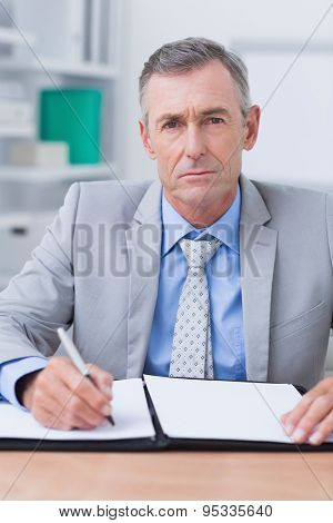 Unhappy businessman looking at camera in his office