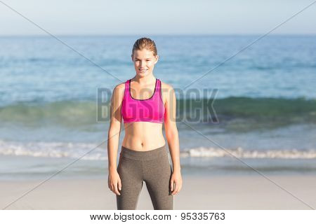 Portrait of beautiful fit woman looking at camera at the beach
