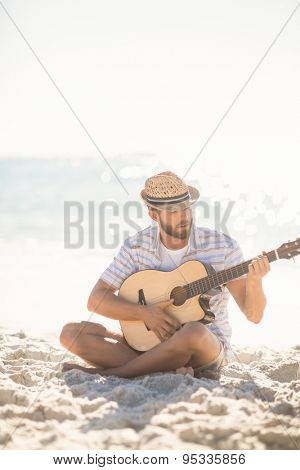 Musician playing guitar on the beach