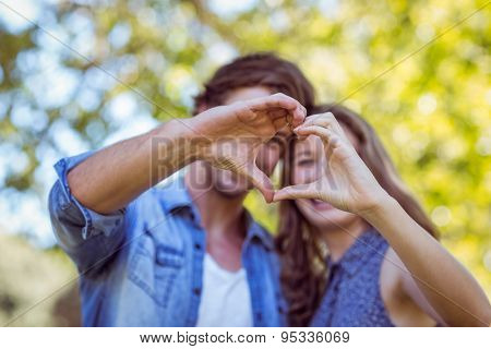 Cute couple in the park making heart shape on a sunny day