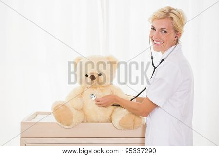Portrait of a blonde doctor with stethoscope and teddy bear in the medical office