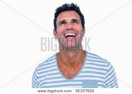 Handsome man laughing and looking away on white background