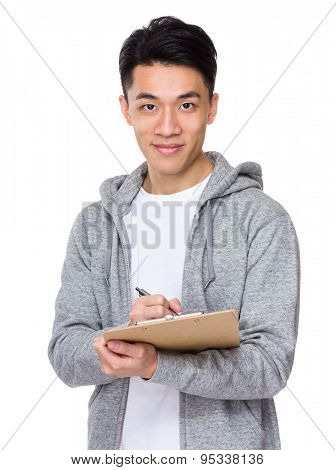 Young man take note on clipboard