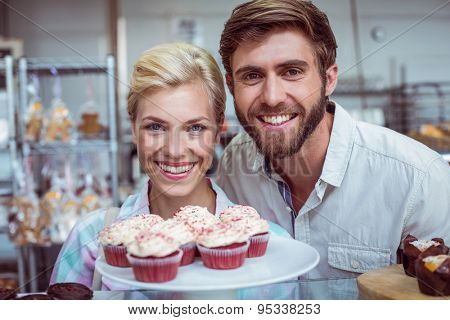 Portrait of a cute couple on a date looking at the camera at the bakery