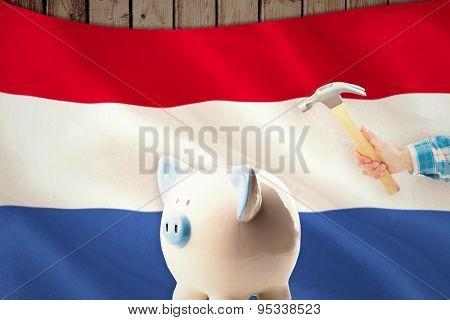 hand holding hammer against digitally generated netherlands national flag
