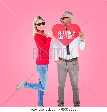 Cool couple holding a red heart together against pink