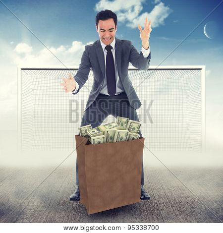 Screaming businessman catching against blue sky