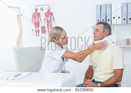Doctor talking to patient wearing neck brace in medical office