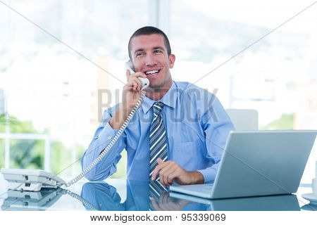 Smiling businessman having a phone call in his office