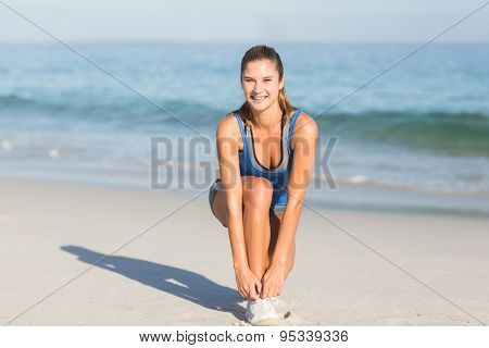 Fit woman tying her shoelace at the beach
