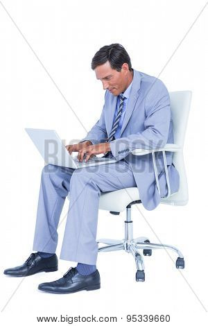 Handsome businessman sitting on a swivel chair and using his laptop against a white screen
