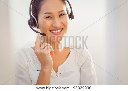 Portrait of a young call centre representative using headset in office