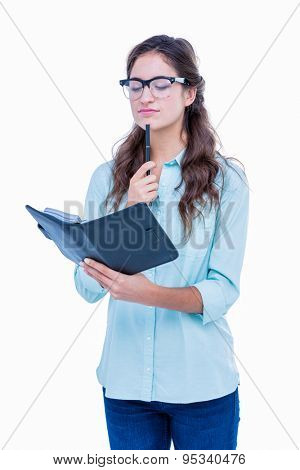 Pretty geeky hipster checking her diary on white background