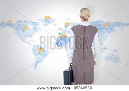 Back turned businesswoman holding a briefcase against world map